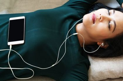 0_Over-head-view-of-beautiful-young-woman-laying-down-on-sofa-using-smartphone-to-listen-the-music